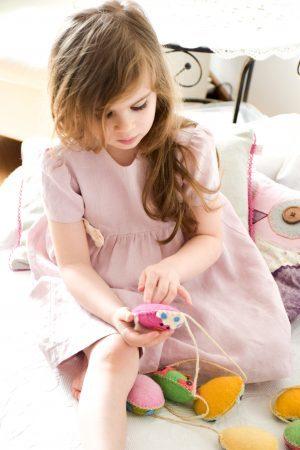 Blado-różowa lniana sukienka dla dziewczynki z białą ecru kokardą